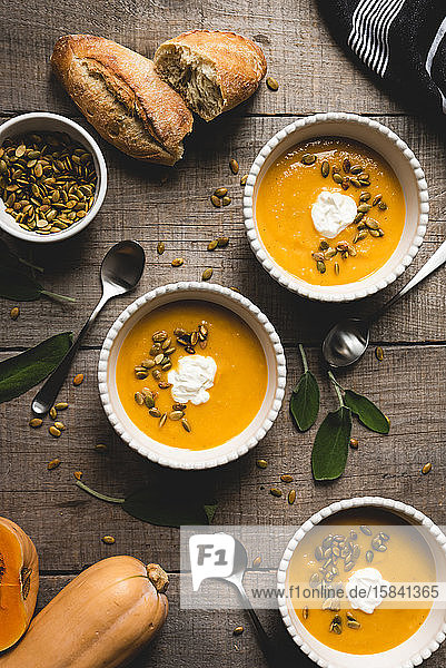 Top view of bowls of butternut squash soup on rustic wooden table.