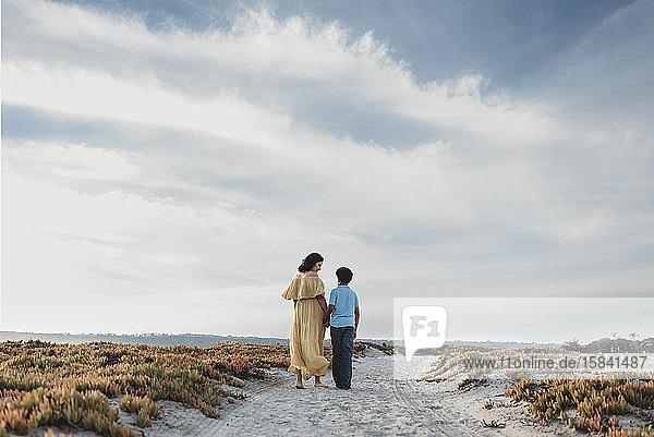 Hinteransicht von Mutter und Sohn beim Spaziergang am Strand vor wolkenblauem Himmel