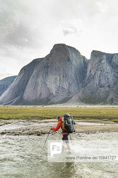 Backpacker crosses river below mountains in Akshayak Pass