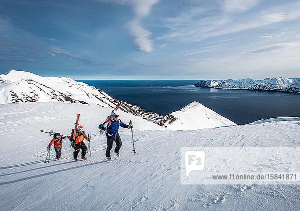 Männer wandern in Island mit Wasser im Hintergrund bergauf