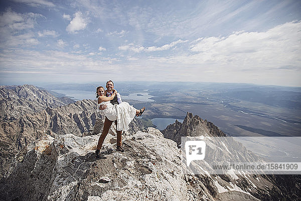 Groom holds bride after getting married on Grand Teton  Wyoming