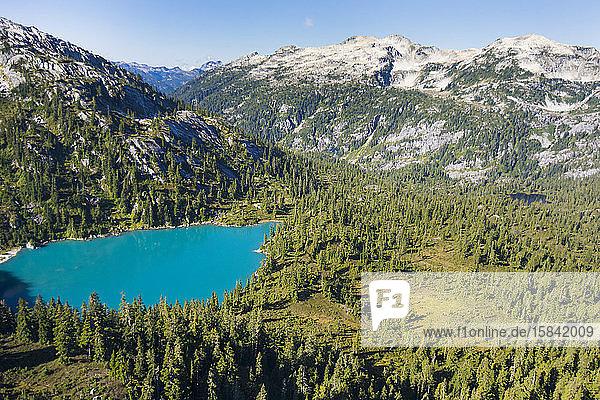 Luftaufnahme des türkisfarbenen Sees in einer Bergkulisse.