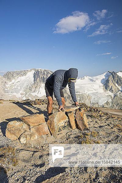 Wanderer baut Felswand als Schutz in den Bergen.