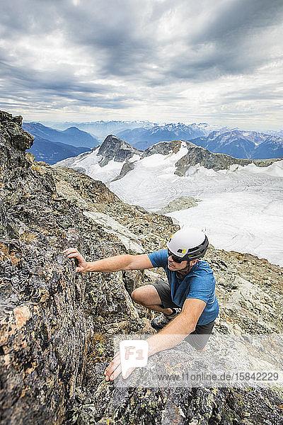 Bergsteiger mit Helm klettert auf den Gipfel eines Berges.