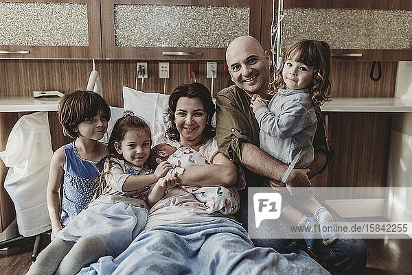Mittelansicht der ganzen Familie  die den neugeborenen Sohn hält und lächelnd im Krankenhaus liegt