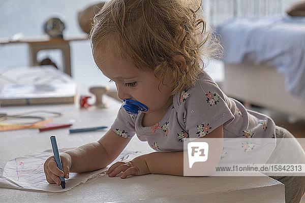 Kleines Mädchen zeichnet mit Farben im Zimmer des Hauses.