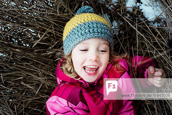 close up of young girl playing on the ground outside in the snow