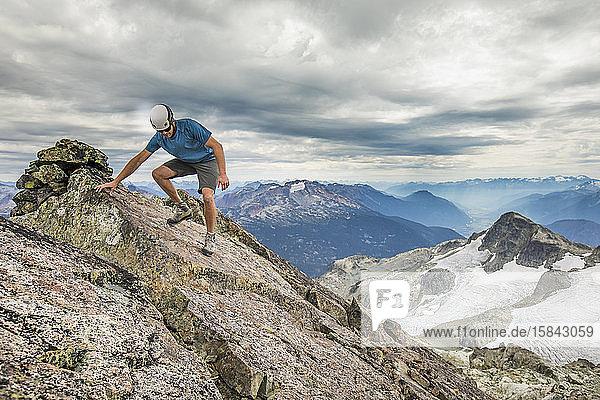 Bergsteiger wandert vorsichtig vom Gipfel eines Berges.