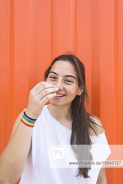 Lächelnde junge Frau lehnt im Freien an einer Wand