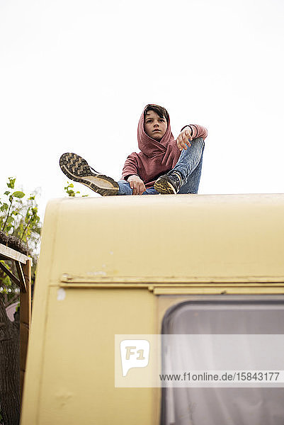 Low view of a young boy sitting on the top of a caravan