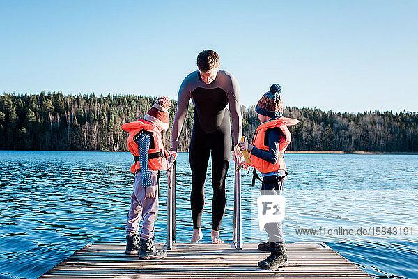 Vater und seine Kinder Kaltwasserschwimmen am Strand in Schweden