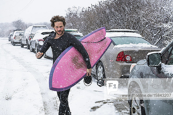 Man preparing to go surfing during winter snow