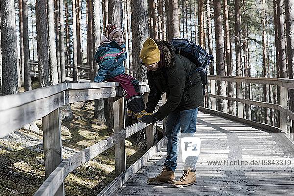 der Vater hilft seiner Tochter beim Schuhanziehen  während sie im Wald spazieren geht