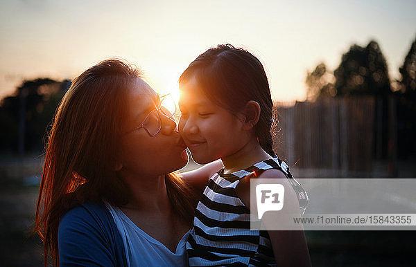 Mutter küsst ihre Tochter bei Sonnenuntergang