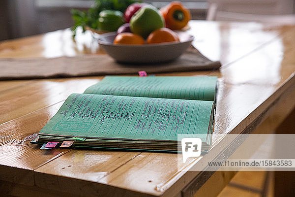Spices and old recipe book on wooden background on kitchen.