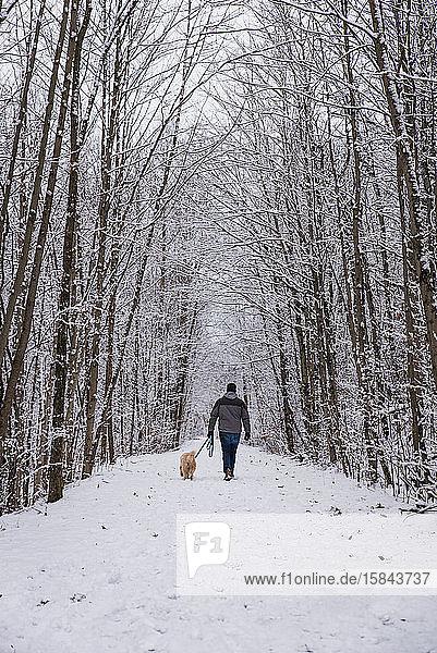 Mann  der an einem Wintertag mit einem Hund auf einem verschneiten Pfad durch den Wald spaziert.