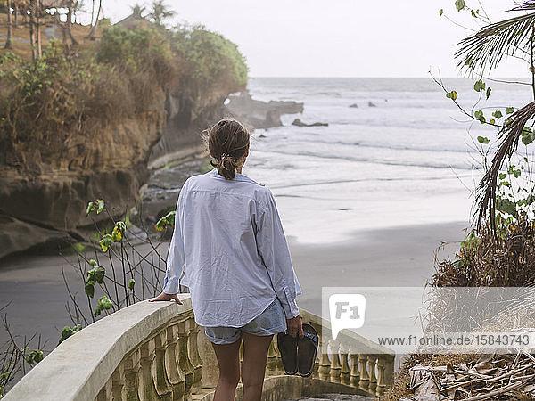 Rückansicht einer Frau  die am Strand eine Treppe hinuntergeht