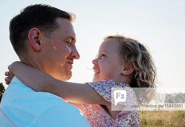 Porträt eines Vaters  der seine Tochter bei Sonnenuntergang draußen lachend hält