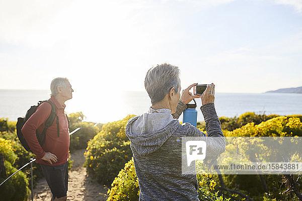 Rückansicht einer älteren Frau  die das Meer mit einem Smartphone fotografiert  während sie neben Pflanzen gegen den Himmel steht