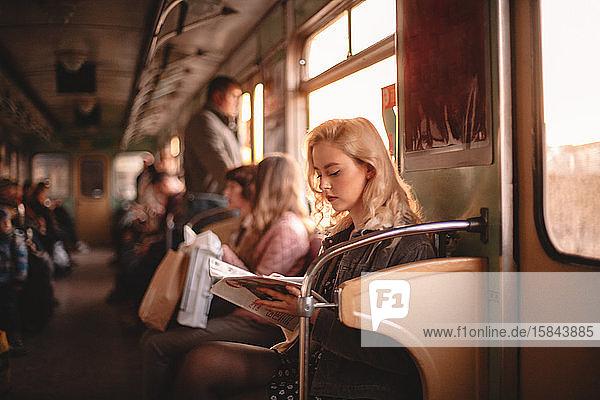 Junge Frau liest Zeitschrift  während sie in der U-Bahn reist