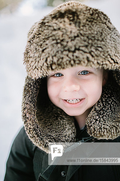 Closeup Toddler Boy Smiling in Furry Hat in Snow