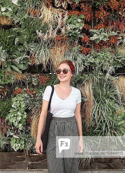 Junge blond lächelnde Frau steht vor Pflanzenwand