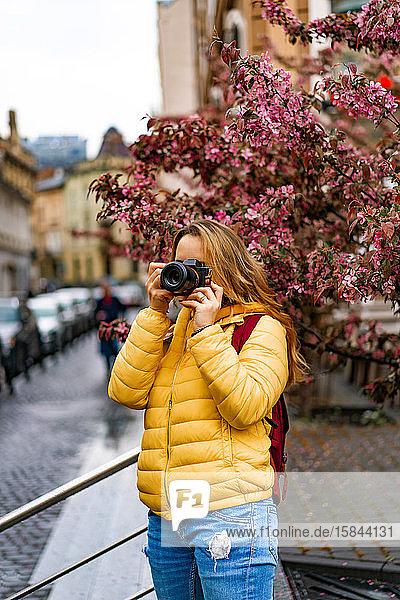 Junge Touristin beim Fotografieren mit der Kamera in der europäischen Altstadt.