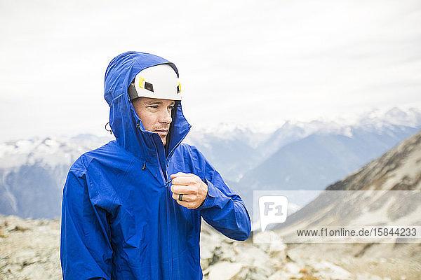 Porträt eines Bergsteigers  der eine Regenjacke zumachen möchte.