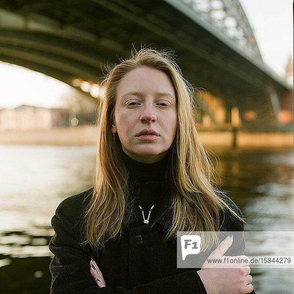 Eine Frau steht bei Sonnenuntergang in der Nähe der Brücke