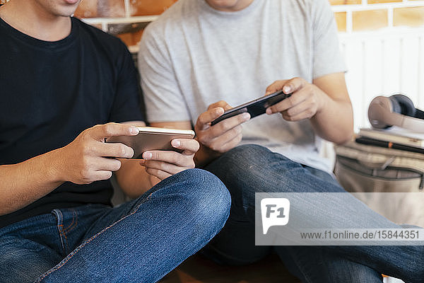 Young teenage men playing mobile game together.