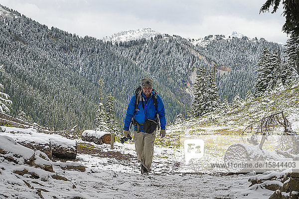 Photographer walking towards camera in the mountains