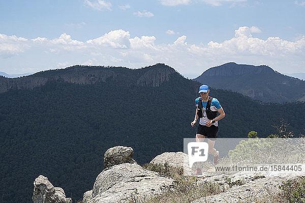 Ein Mann rennt auf einem felsigen Gelände in einem Berggebiet in Mexiko