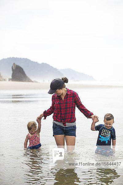 Mutter watet mit ihren beiden Kindern durchs Wasser.