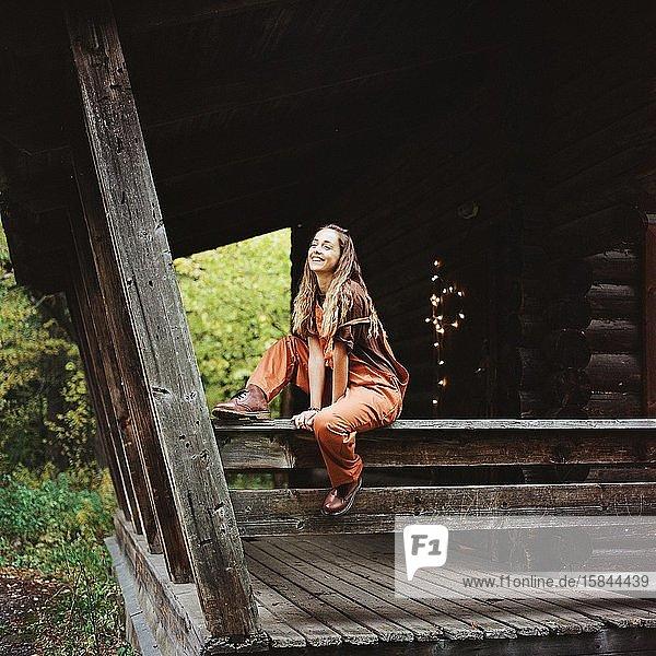 Frau sitzt neben altem Holzhaus und schaut weg