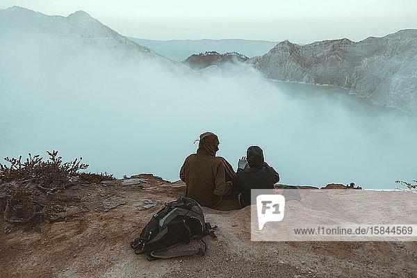 Zwei Wanderer sitzen und schauen auf den Ijen-See