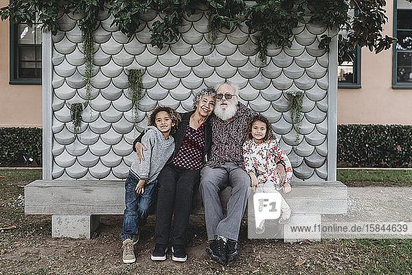 Porträt der Großeltern  die mit niedlichen Zwillingsenkelkindern draußen sitzen