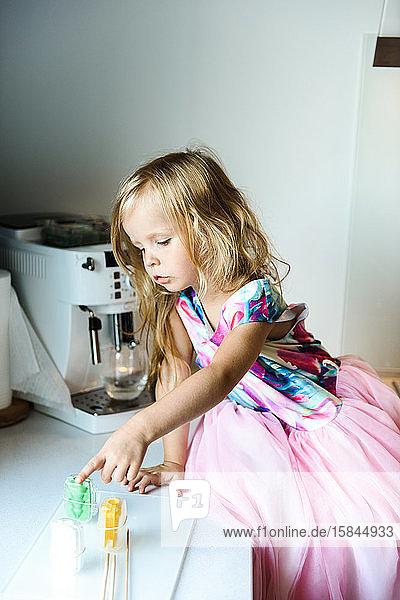 Kleines Mädchen auf einem Tisch in der Küche