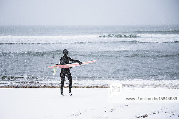 Frau geht im Winterschnee surfen