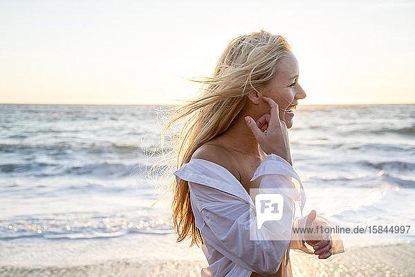 Teenager-Mädchen lacht am Strand bei Sonnenuntergang