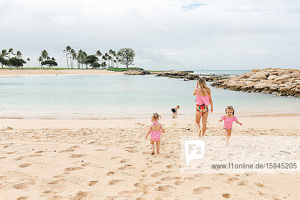 mother with children playing on beach