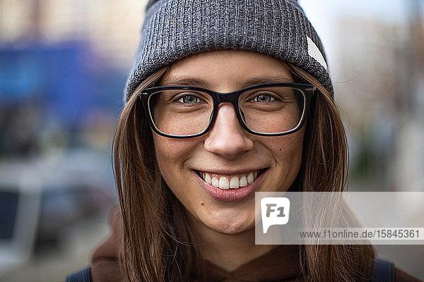 Fröhliche Frau auf der Straße trinkt Morgenkaffee bei Sonnenschein