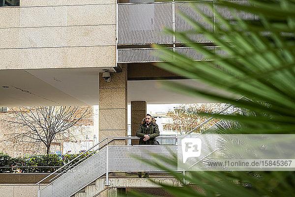Bärtiger Hipster-Mann entspannt sich auf einer Treppe in einem Gebäudekomplex