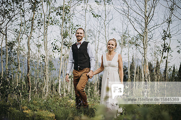glückliche Frischvermählte halten sich bei einem Spaziergang durch den Birkenwald an den Händen  Wyoming