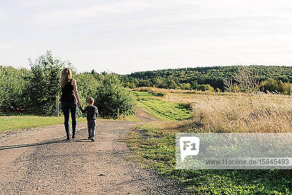 Kleiner Junge geht mit seiner Mutter spazieren.