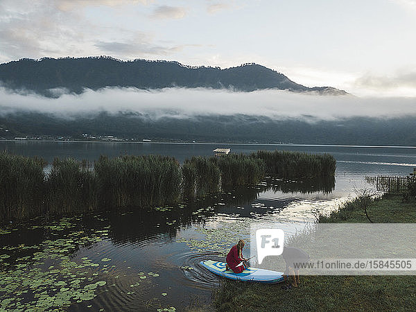 Paar mit Surfbrett in der Nähe des Bratan-Sees