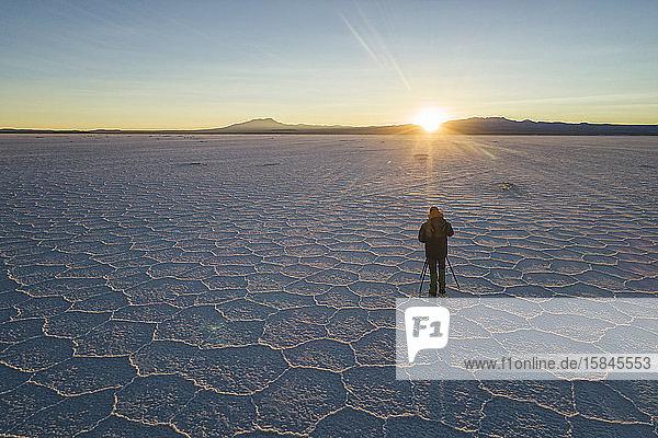 Mann  der den Sonnenaufgang über der Salzfläche fotografiert