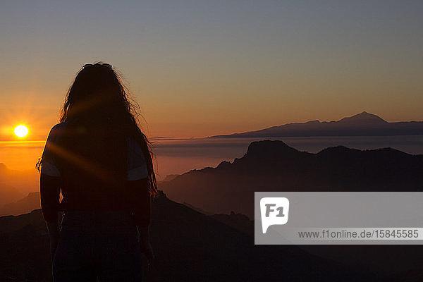 Frau mit langem Gehör  die den Sonnenuntergang betrachtet  während sie auf einem Berg steht