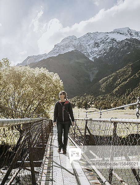 Wanderin wandert auf Hängebrücke über den Fluss in Mount Aspiring.