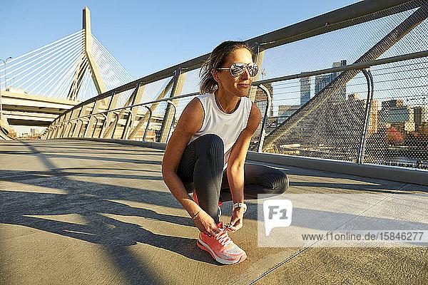 Eine sportliche Frau bindet ihren Schuh vor der Zakim-Brücke in Boston