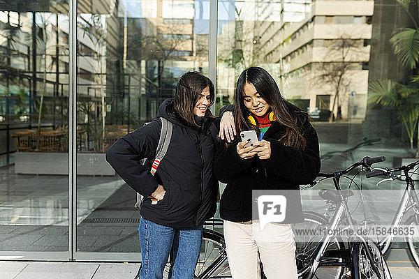 Zwei Freunde schauen auf das Smartphone  das in der Glaswand des Gebäudes steht